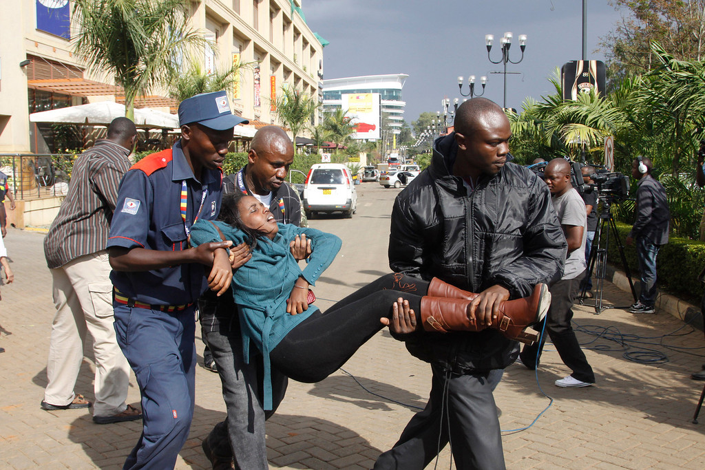 Description of . A security officer helps a wounded woman outside the Westgate Mall in Nairobi, Kenya Saturday, Sept. 21, 2013, after gunmen threw grenades and opened fire during an attack that left multiple dead and dozens wounded.  (AP Photo/Khalil Senosi)