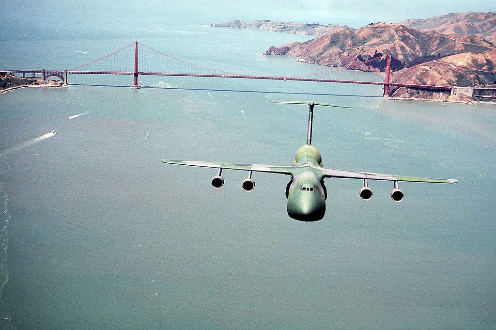 Description of . An air-to-air front view of a C-5A Galaxy aircraft, in a camouflage paint scheme, as it flies over the San Francisco Bay. The Golden Gate Bridge can be seen in the background. (Photo by USAF, Getty Images)