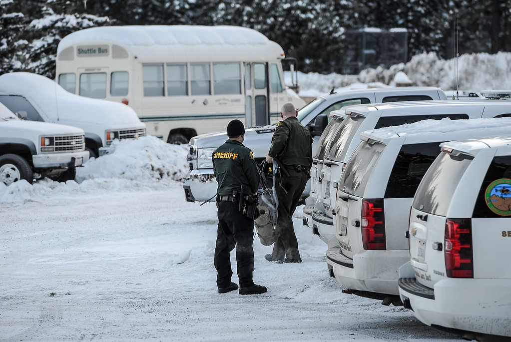 Description of . A sheriff's deputy waits for his partners as they prepare to leave the command post at Bear Mountain Resort at start of day four in the search for fugitive ex-cop Christopher Dorner in Big Bear on Sunday, Feb. 10, 2013. (Rachel Luna / Staff Photographer)