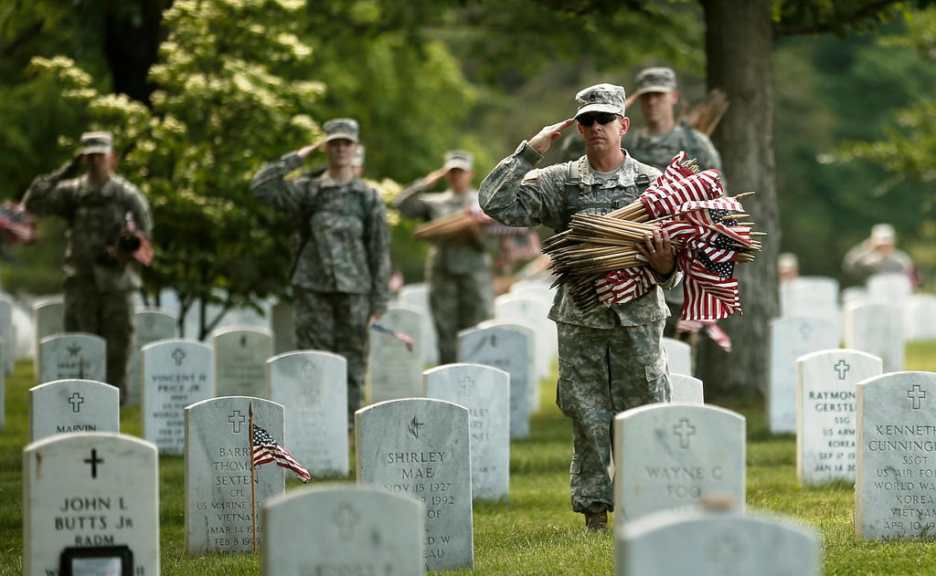 """Description of . Soldiers salute as \""""Taps\"""" is played during a military funeral nearby as they were placing flags on graves at Arlington National Cemetery in Virginia May 23, 2013. The annual \""""Flags-In\"""" ceremony is held ahead of Memorial Day to honor the nation\'s fallen members of the military. Soldiers of the Third U.S. Infantry Regiment (The Old Guard) place a small American flag before each grave marker for more than 220,000 graves.    REUTERS/Kevin Lamarque"""