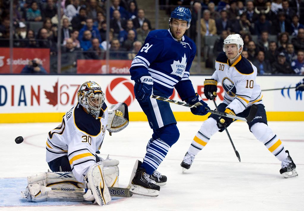 . Buffalo Sabres defenseman Christian Ehrhoff (10) watches as goaltender Ryan Miller makes a save under pressure from Toronto Maple Leafs left winger James van Riemsdyk (21) during the second period of their NHL hockey game, Thursday, Feb. 21, 2013, in Toronto. (AP Photo/The Canadian Press, Frank Gunn)
