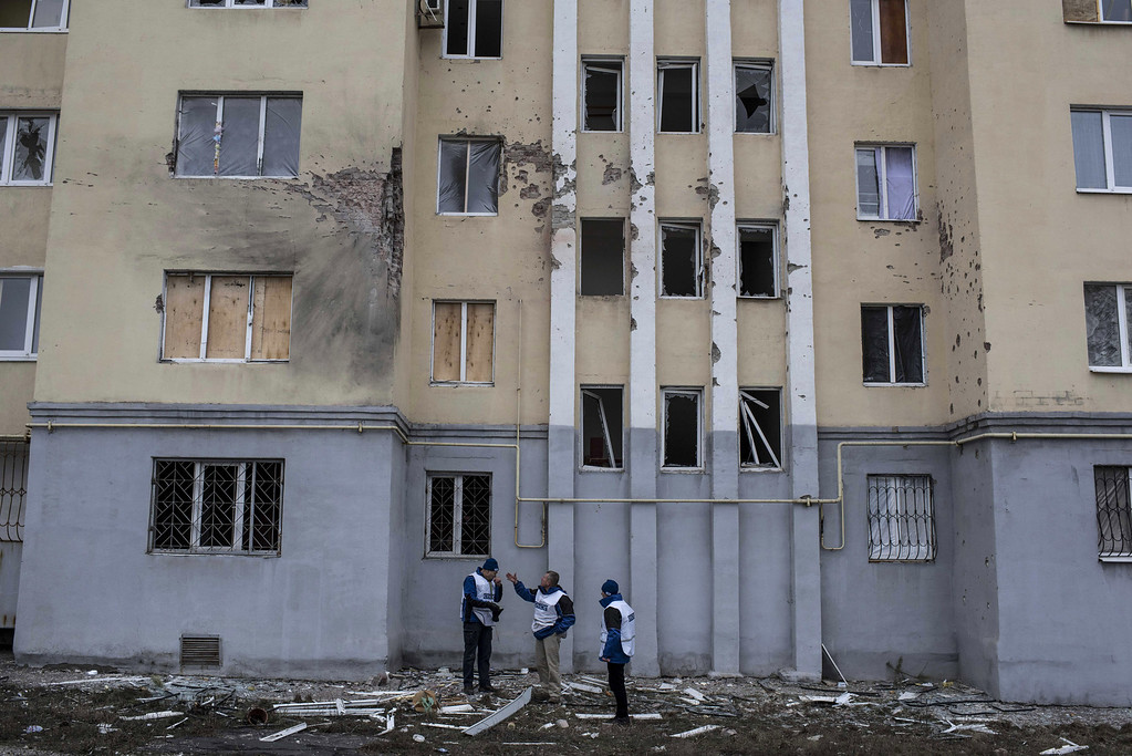 Description of . Organization for Security and Co-operation in Europe (OSCE) monitors investigate outside an apartment building damaged in Saturday's shelling in which scores of people were killed and injured in Mariupol, Ukraine, Tuesday, Jan. 27, 2015. European Union leaders are threatening fresh sanctions against Russia because of what it sees as