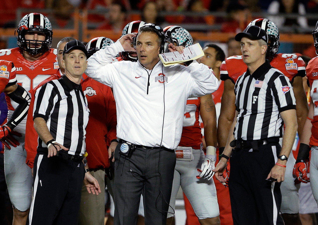 Description of . Ohio State coach Urban Meyer stands with officials as they wait for a ruling on the field during the first half of the Orange Bowl NCAA college football game against Clemson, Friday, Jan. 3, 2014, in Miami Gardens, Fla. (AP Photo/Lynne Sladky)