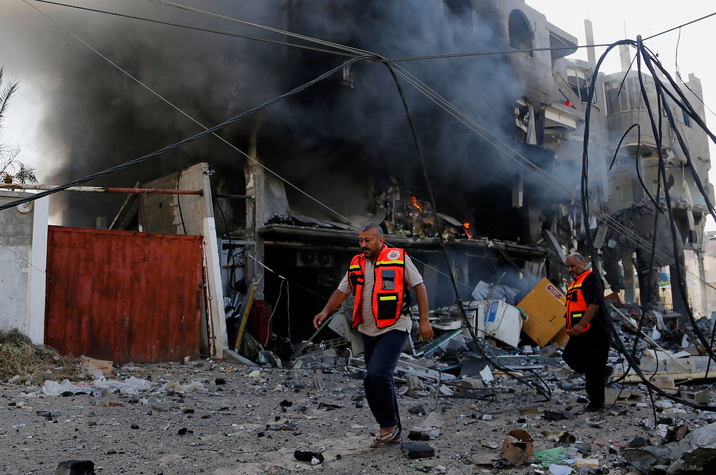 Description of . Palestinian firefighters inspects the damage of a destroyed milk factory after it was hit by an Israeli airstrike in Gaza City, Thursday, July 31, 2014. Israel said Thursday it has called up another 16,000 reservists, allowing it to potentially widen its Gaza operation against the territory's Hamas rulers in a three-week-old war that has killed more than 1,300 Palestinians and more than 50 Israelis. (AP Photo/Hatem Moussa)