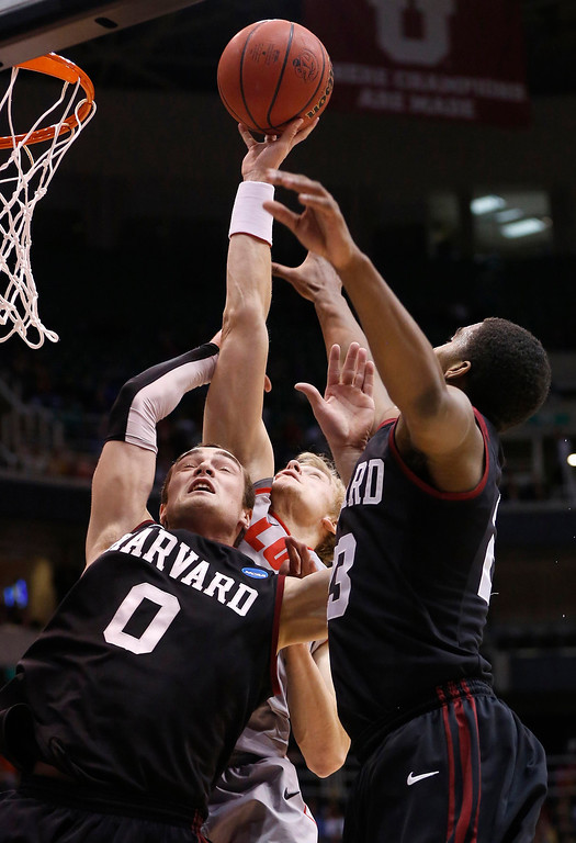 . New Mexico guard Hugh Greenwood (3) attempts a shot while defended by Harvard guards Laurent Rivard (0) and Wesley Saunders (23) during the first half of their second round NCAA tournament basketball game in Salt Lake City, Utah, March 21, 2013. REUTERS/Jim Urquhart