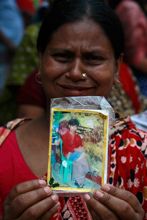 Description of . A relative holds a picture of a missing garment worker, who was working in the Rana Plaza building when it collapsed, in Savar, 30 km (19 miles) outside Dhaka April 24, 2013.  REUTERS/Andrew Biraj