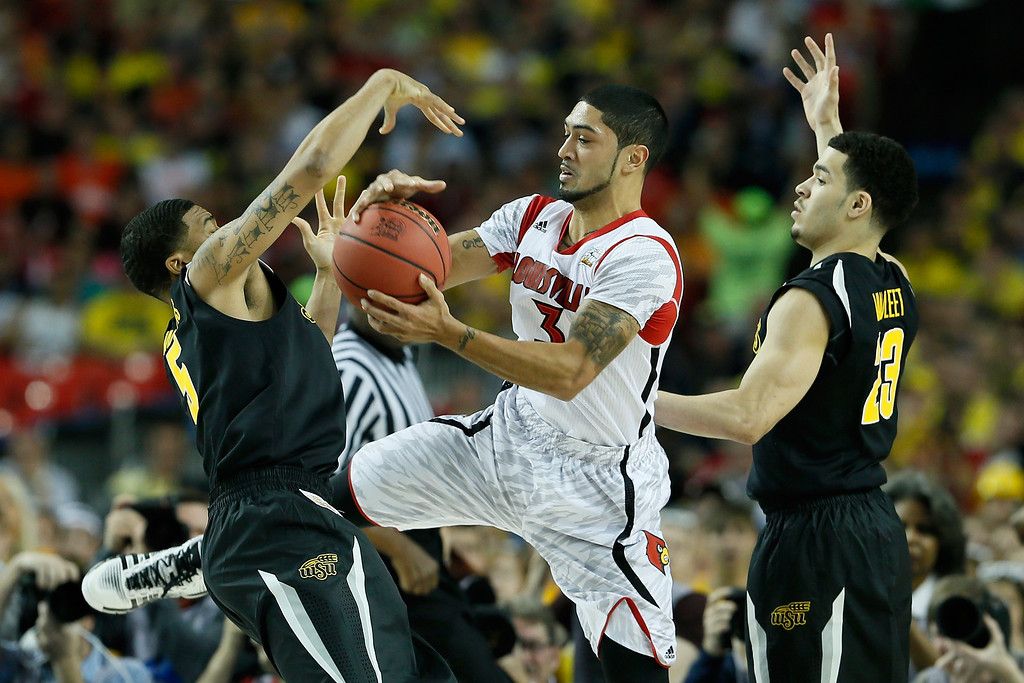 Description of . ATLANTA, GA - APRIL 06:  Peyton Siva #3 of the Louisville Cardinals with the ball between Demetric Williams #5 and Fred VanVleet #23 of the Wichita State Shockers in the first half during the 2013 NCAA Men's Final Four Semifinal at the Georgia Dome on April 6, 2013 in Atlanta, Georgia.  (Photo by Kevin C. Cox/Getty Images)