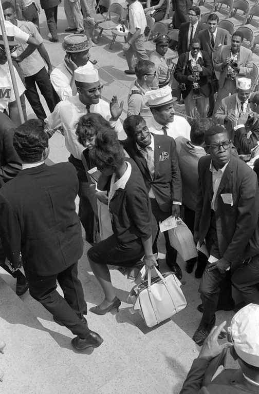 Description of . Sammy Davis, Jr., waving to people as he walks past marshalls at the Lincoln Memorial during the March on Washington. Aug. 28, 1963. (Warren K. Leffler - Library of Congress Prints and Photographs Division)