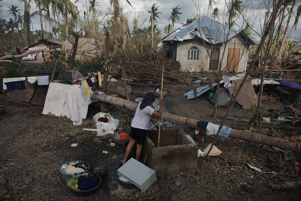 Description of . A typhoon victim wash her clothes in Balire on November 18, 2013. The United Nations has confirmed at least 4,500 killed in the disaster, which brought five-meter (16-foot) waves to Tacloban, flattening nearly everything in their path as they swept hundreds of meters across the low-lying land. NICOLAS ASFOURI/AFP/Getty Images