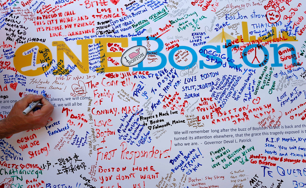 Description of . A person writes on a poster at a makeshift memorial in Copley Square on Boylston Street in Boston, Wednesday, April 24, 2013. Traffic was allowed to flow all the way down Boylston Street on Wednesday morning for the first time since two explosions on April 15.(AP Photo/Michael Dwyer)