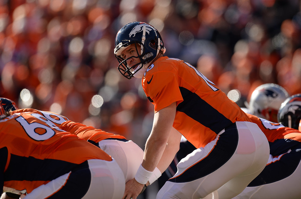 Description of . Denver Broncos quarterback Peyton Manning (18) waits for the snap at the line in the second quarter. The Denver Broncos take on the New England Patriots in the AFC Championship game at Sports Authority Field at Mile High in Denver on January 19, 2014. (Photo by Hyoung Chang/The Denver Post)