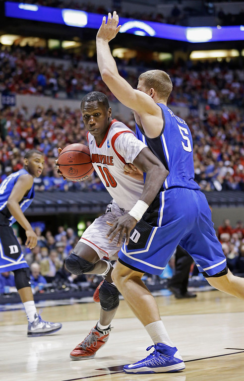 Description of . Louisville's Gorgui Dieng (10) drives to the basket past Duke's Mason Plumlee (5) during the first half of the Midwest Regional final in the NCAA college basketball tournament, Sunday, March 31, 2013, in Indianapolis. (AP Photo/Michael Conroy)