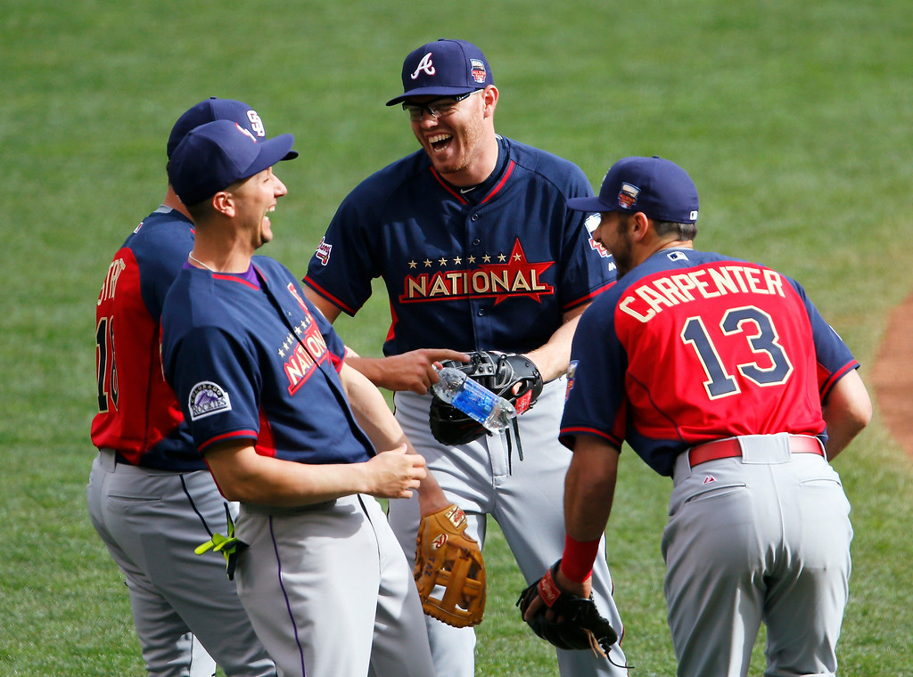 Description of . National League infielder Freddie Freeman, of the Atlanta Braves, center, laughs with teammates during batting practice for the MLB All-Star baseball game, Monday, July 14, 2014, in Minneapolis. (AP Photo/Paul Sancya)