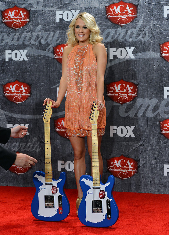 Description of . LAS VEGAS, NV - DECEMBER 10:  Singer Carrie Underwood poses in the press room with her awards for Female Artist of the Year and Single by a Vocal Collaboration during the 2012 American Country Awards at the Mandalay Bay Events Center on December 10, 2012 in Las Vegas, Nevada.  (Photo by Frazer Harrison/Getty Images)