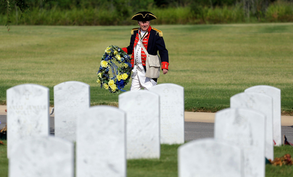 Description of . A member of the Sons of the American Revolution San Antonio Chapter carries a wreath to a Fourth of July Patriotic Ceremony at Fort Sam Houston National Cemetery, Thursday, July 4, 2013, in San Antonio. (AP Photo/Eric Gay)