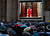 People watch on a video monitor in St. Peter's Square as Monsignor Guido Marini, master of liturgical ceremonies, closes the double doors to the Sistine Chapel after shouting