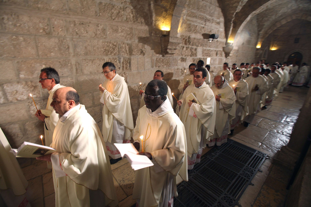Description of . Clergymen attends the Christmas Midnight Mass led by Foud Twal, the Latin Patriarch of the Holy Land, in Saint Catherine's Church at the Church of the Nativity, where Christians believe the Virgin Mary gave birth to Jesus Christ, on December 25, 2013 in Bethlehem, West Bank. In the West Bank town of Bethlehem, Jerusalem's Latin patriarch Fuad Twal celebrated a midnight mass attended by Palestinian president Mahmud Abbas.   Thousands of pilgrims and tourists made their way past Israel's controversial separation wall to reach the Palestinian hilltop town, where snow remains on the ground from a rare winter blizzard this month.  MUSA AL-SHAER/AFP/Getty Images