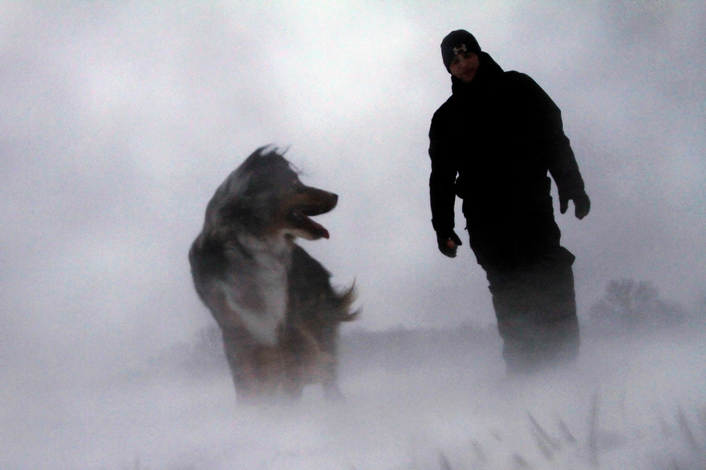Description of . Zach Stead and his dog Tucker brave high winds, blowing snow and freezing temperatures while walking outside Thursday, Dec. 20, 2012 in Springfield, Ill. The first widespread snowstorm of the season crawled across the Midwest on Thursday, with whiteout conditions stranding holiday travelers and sending drivers sliding over slick roads, including into a fatal 25-vehicle pileup in Iowa. (AP Photo/Seth Perlman)