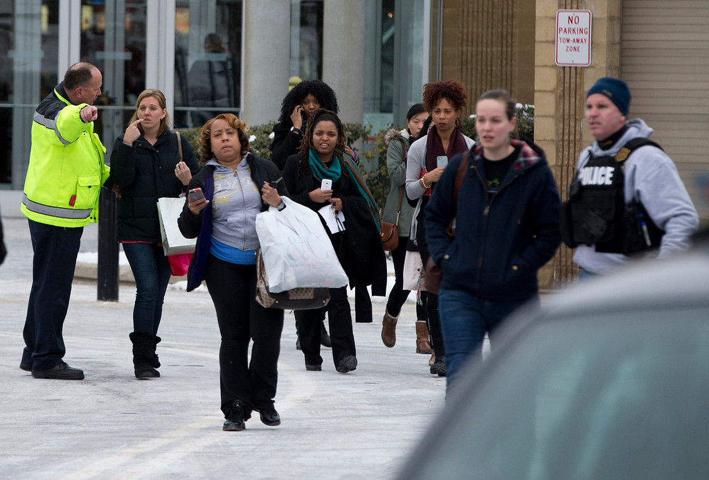 Description of . Police and law enforcement evacuate the Mall of Columbia after a shooting on Saturday, Jan. 25, 2014 in Columbia, Md. Police say three people died in a shooting at the mall in suburban Baltimore, including the presumed gunman. (AP Photo/ Evan Vucci)