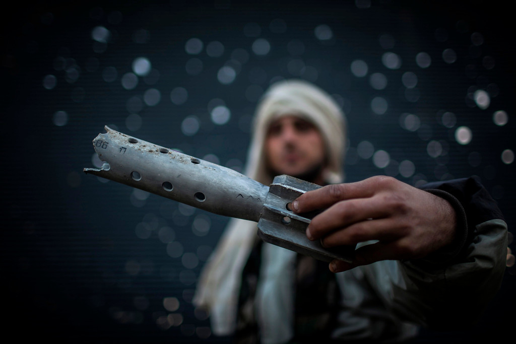Description of . FILE - A Free Syrian Army fighter displays a damaged ordinance in Aleppo, Syria, Tuesday, Jan. 15, 2013. (AP Photo/Andoni Lubaki, File)