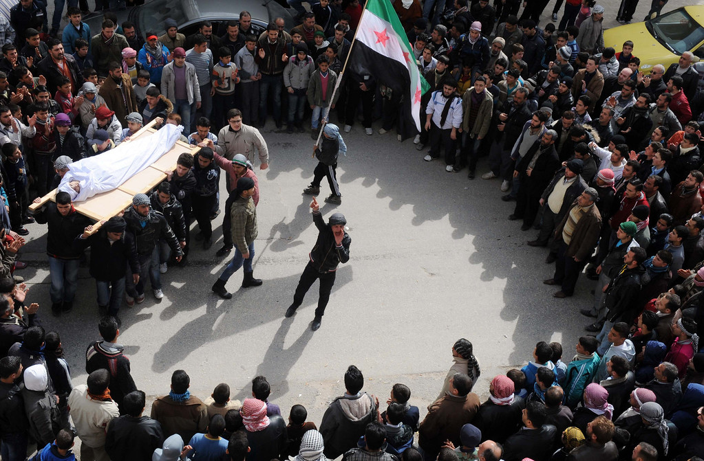 Description of . Syrian mourners, one carrying the pre-Baath national flag adopted by the rebel movement, carry the body of a youth reportedly killed in violence in the northwestern Idlib region before his burial on February 23, 2012. Three Syrian soldiers were killed and seven others wounded in a bomb at the southern entrance to the flashpoint city of Idlib , according to the official Syrian Arab News Agency BULENT KILIC/AFP/Getty Images