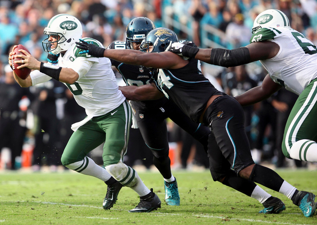 Description of . New York Jets quarterback Mark Sanchez (L) is tackled by Jacksonville Jaguars defensive lineman Jeremy Mincey (C) during the second half of their NFL football game in Jacksonville, Florida December 9, 2012. REUTERS/Daron Dean