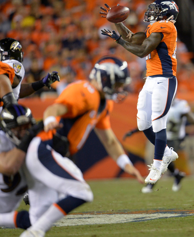 Description of . Denver Broncos running back Ronnie Hillman (21) makes a first down catch in the third quarter, why Denver Broncos quarterback Peyton Manning (18) gets taken down in the foreground.  (Photo by Joe Amon/The Denver Post)