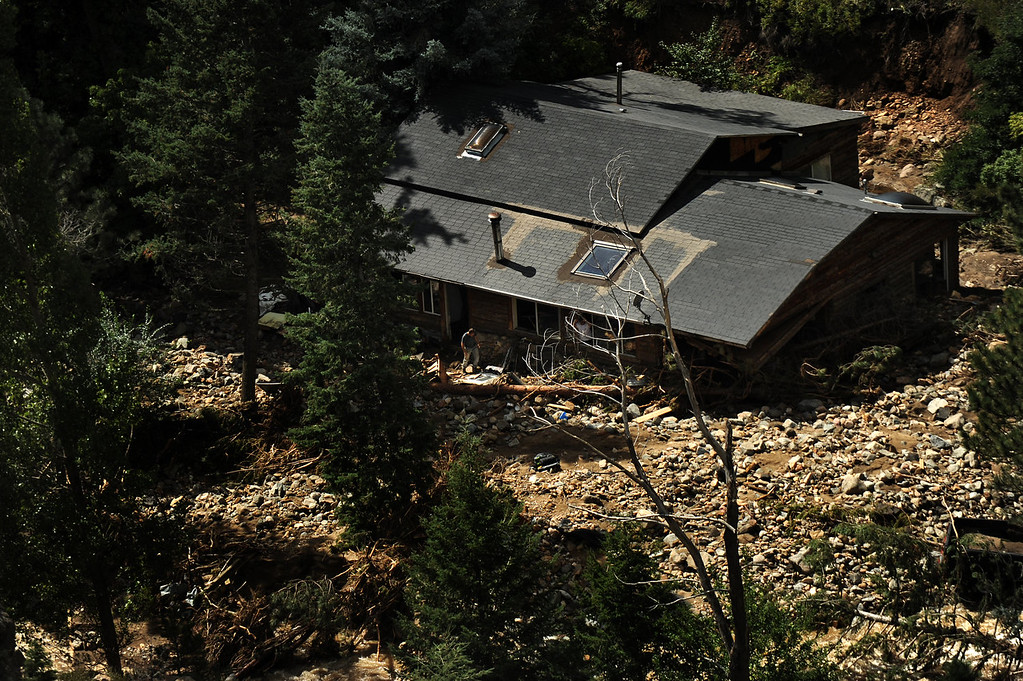 Description of . A man near a flood damaged as seen from a UH-60 Black Hawk during search grid flights of the foothills west of Boulder by members of the 2-4 GSAB with the 4th ID of Fort Carson September 17, 2013 Boulder, CO. (Photo By Joe Amon/The Denver Post)