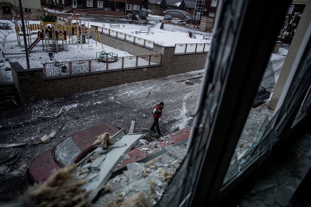 Description of . A Ukrainian man walks through the debris produced after the Ukrainian Army hit a building in Voroshilovsky area, center of Donetsk, Ukraine. Sunday, Jan. 18, 2015. The separatist stronghold, Donetsk, was shaken by intense outgoing and incoming artillery fire as a bitter battle raged for control over the city's airport. Streets in the city, which was home to 1 million people before unrest erupted in spring, were completely deserted and the windows of apartments in the center rattled from incessant rocket and mortar fire. (AP Photo/Manu Brabo)