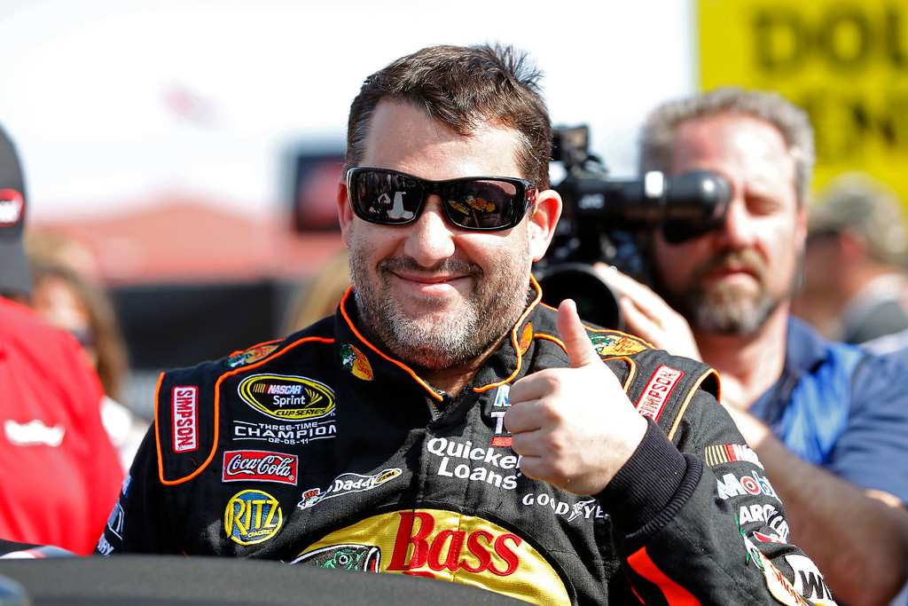 Description of . Tony Stewart gives the thumbs up as he gets in his car for the Budweiser Duel 1 NASCAR Sprint Cup Series auto race at Daytona International Speedway, Thursday, Feb. 21, 2013, in Daytona Beach, Fla. (AP Photo/Terry Renna)