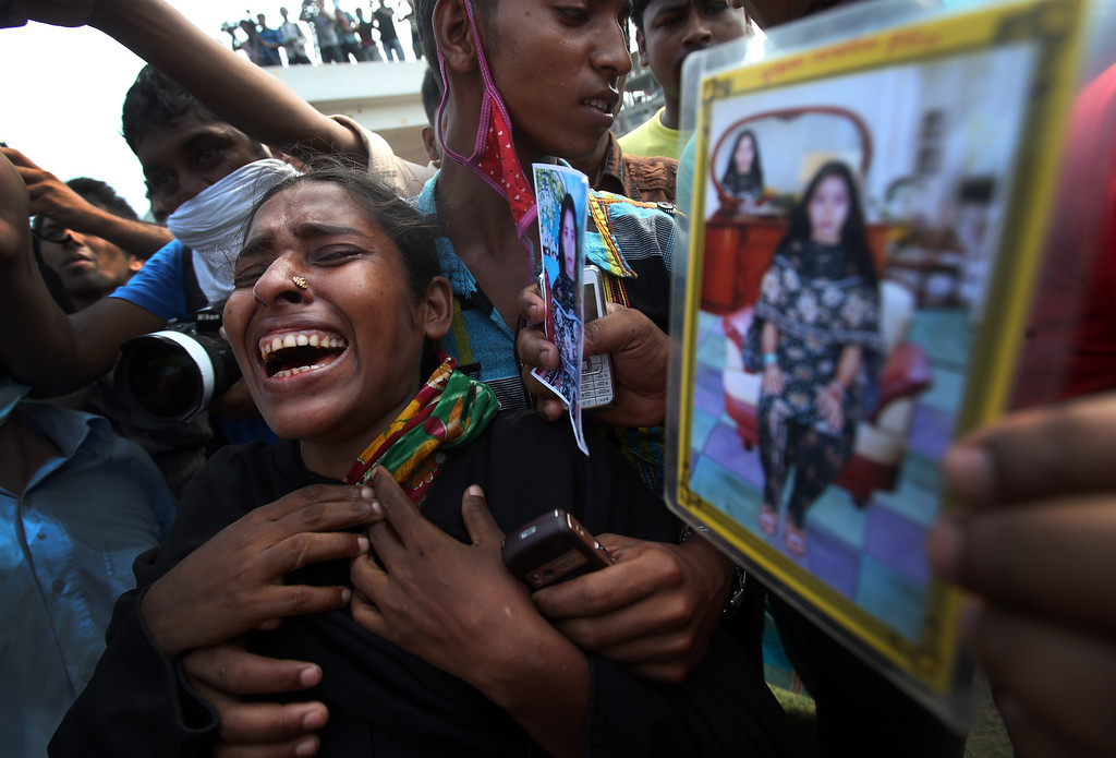 Description of . A woman mourns as she arrived in hopes to find her sister among unclaimed bodies brought to a cemetery from the garment factory building collapse in preparation for a mass burial on Wednesday May 1, 2013 in Dhaka, Bangladesh. AP Photo/Wong Maye-E)