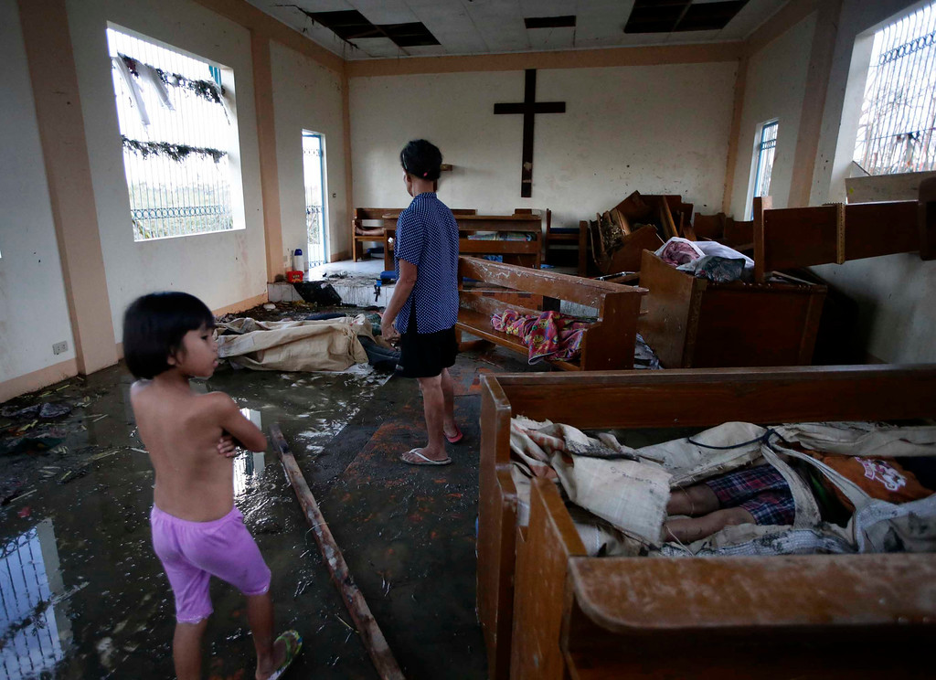 Description of . In this Saturday, Nov. 9, 2013 file photo, residents look at bodies brought inside a damaged chapel day after powerful Typhoon Haiyan slammed Tacloban city, in Leyte province in central Philippines. Haiyan slammed the island nation with a storm surge two stories high and some of the highest winds ever measured in a tropical cyclone. An untold number of homes were blown away, and thousands of people are feared dead. (AP Photo/Bullit Marquez, File)