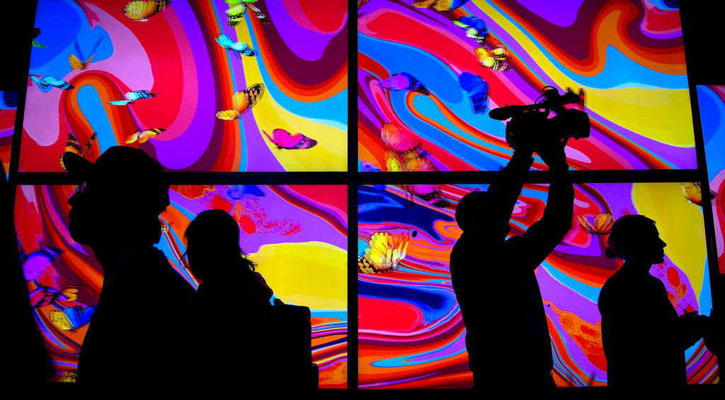 Description of . Trade show attendees pass by an LG Ultra HD 3D wall display at the International Consumer Electronics Show, Wednesday, Jan. 8, 2014, in Las Vegas. (AP Photo/Julie Jacobson)
