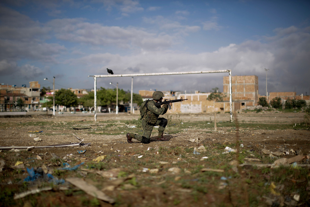 Description of . A navy soldier patrols on a soccer field during an operation to occupy the Mare slum complex in Rio de Janeiro, Brazil, Saturday, April 5, 2014. More than 2,000 Brazilian Army soldiers moved into the Mare slum complex early Saturday in a bid to improve security and drive out the heavily armed drug gangs that have ruled the sprawling slum for decades.(AP Photo/Felipe Dana)
