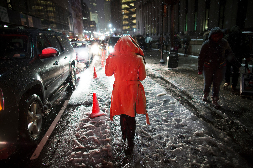 Description of . Snow falls on a pedestrian as she leaves the Rag & Bone Fall 2013 fashion collection show during Fashion Week, Friday, Feb. 8, 2013, in New York. Snow began falling across the Northeast on Friday, ushering in what was predicted to be a huge, possibly historic blizzard and sending residents scurrying to stock up on food and gas up their cars. (AP Photo/John Minchillo)