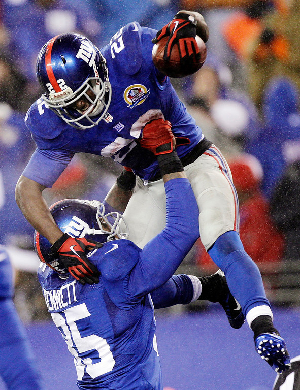 Description of . New York Giants running back David Wilson (22) is hoisted into the air by Martellus Bennett after scoring on a 52-yard touchdown run during the fourth quarter of an NFL football game, Sunday, Dec. 9, 2012, in East Rutherford, N.J. The Giants won 52-27. (AP Photo/Kathy Willens)