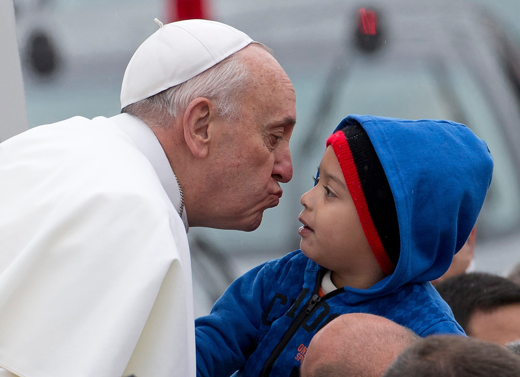 Description of . Pope Francis reaches out to kiss a child as he arrives to the Aparecida Basilicia in Aparecida, Brazil, Wednesday, July 24, 2013.  (AP Photo/Domenico Stinellis)