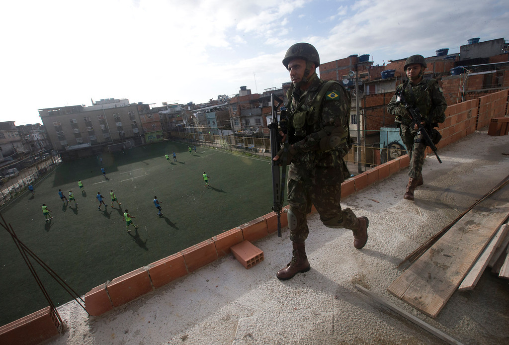 Description of . Army soldiers walk at a roof while residents play soccer during an operation to occupy the Mare slum complex in Rio de Janeiro, Brazil, Saturday, April 5, 2014. More than 2,000 Brazilian Army soldiers moved into the Mare slum complex early Saturday in a bid to improve security and drive out the heavily armed drug gangs that have ruled the sprawling slum for decades. (AP Photo/Silvia Izquierdo)