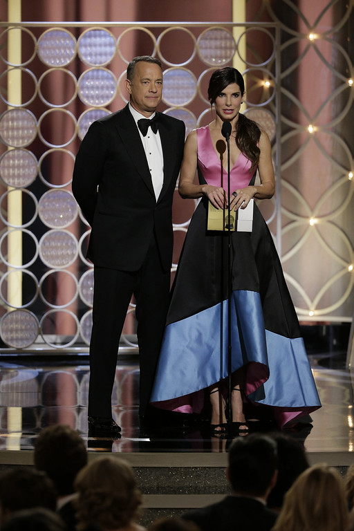 Description of . In this handout photo provided by NBCUniversal, Presenters Tom Hanks and Sandra Bullock speak onstage during the 71st Annual Golden Globe Award at The Beverly Hilton Hotel on January 12, 2014 in Beverly Hills, California.  (Photo by Paul Drinkwater/NBCUniversal via Getty Image)