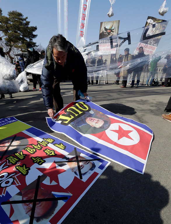 Description of . A South Korean activist holds North Korean flags before releasing them with huge helium balloons during an anti-North Korea rally denouncing North Korea's third nuclear test at the Imjingak Pavilion near the border village of the Panmunjom (DMZ) that separates the two Koreas since the Korean War, in Paju, north of Seoul, South Korea, Saturday, Feb. 16, 2013. They released 200,000 propaganda leaflets across the border to denounce the North Korea's third nuclear test and late leader Kim Jong Il's birthday on Saturday.  (AP Photo/Lee Jin-man)