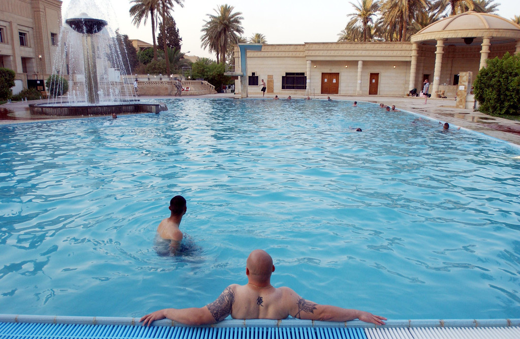 Description of . Off-duty U.S. soldiers enjoy Saddam Hussein\'s swimming pool at the Republican Palace July 14, 2003 in Baghdad, Iraq.  (Photo by Marco Di Lauro/Getty Images)