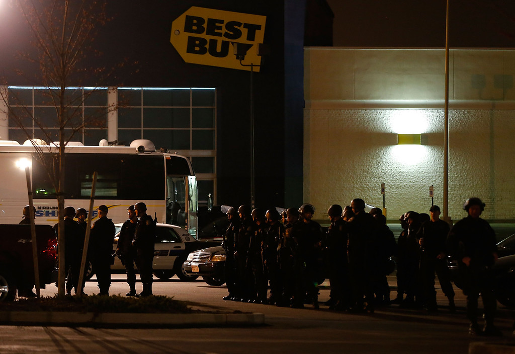 Description of . WATERTOWN, MA - APRIL 19: Boston Police gather in the parking lot in front of a Best Buy store on April 19, 2013 near the Watertown Mall in Watertown, Massachusetts. (Photo by Jared Wickerham/Getty Images)