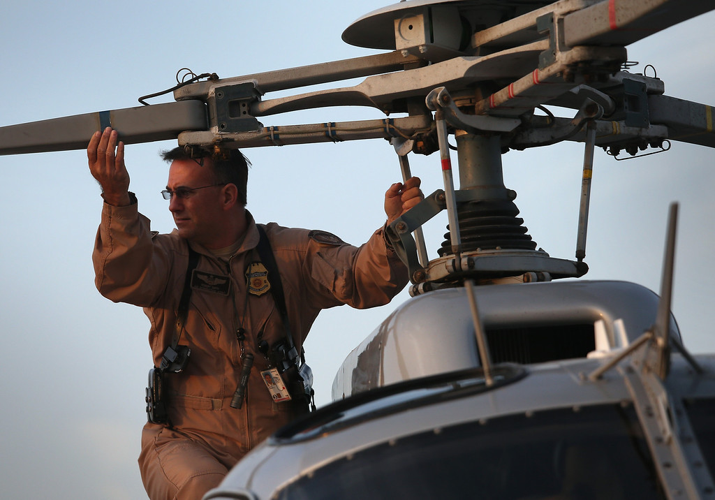 Description of . McAllen, TX - APRIL 11:  U.S. Office of Air and Marine (OAM), pilot Rob Smith performs a pre-flight check on an Astar B-2 helicopter before flying a patrol along the U.S.-Mexico border on April 11, 2013 in McAllen, Texas. The OAM, which assists U.S. Border Patrol agents from the air in locating undocumented immigrants and drug smugglers, has cut back flights drastically due to federal sequestration budget cuts. According to the U.S. Border Patrol, undocumented immigrant crossings have increased more than 50 percent in Texas\' Rio Grande Valley sector in the last year. Border Patrol agents say they have also seen an additional surge in immigrant traffic since immigration reform negotiations began this year in Washington D.C. Proposed refoms could provide a path to citizenship for many of the estimated 11 million undocumented workers living in the United States.  (Photo by John Moore/Getty Images)