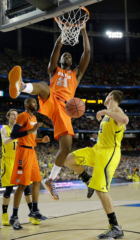 Description of . Syracuse's Rakeem Christmas (25) dunks the ball as Michigan's Mitch McGary (4) looks on during the second half of the NCAA Final Four tournament college basketball semifinal game Saturday, April 6, 2013, in Atlanta. (AP Photo/David J. Phillip)