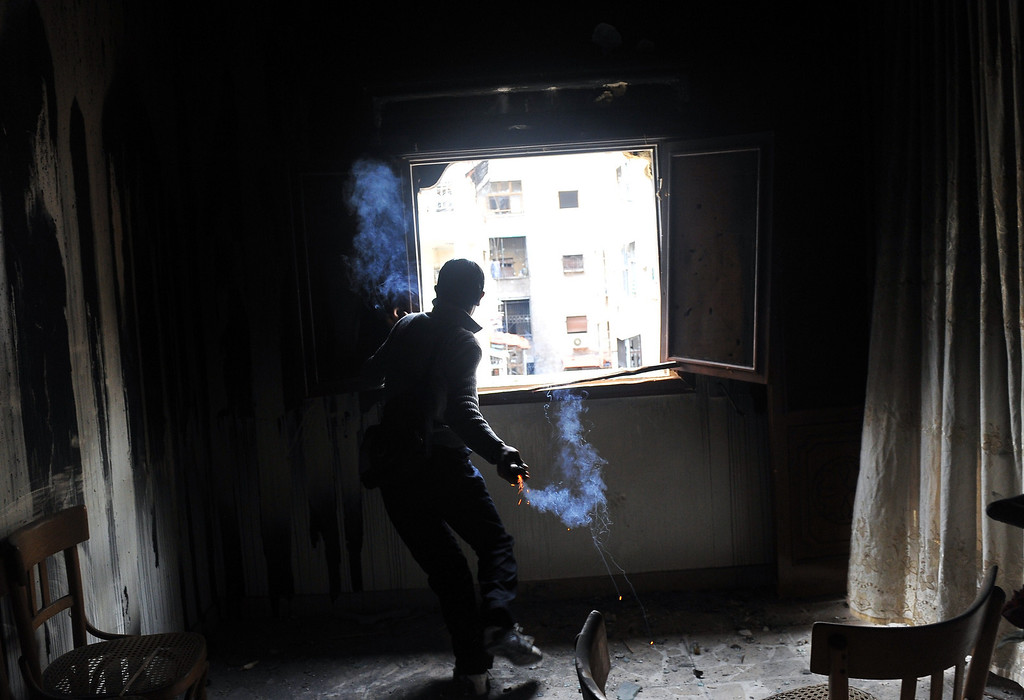 Description of . A rebel fighter throws a homemade grenade through a window toward Syrian government forces at a flat in the Salaheddine neighborhood of Aleppo on February 16, 2013. More than 300 people were abducted by armed groups in northwestern Syria over two days in an unprecedented string of sectarian kidnappings, a watchdog and residents said.  BULENT KILIC/AFP/Getty Images