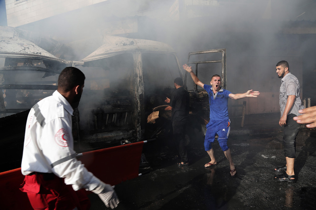 Description of . A man shouts for help after two people were killed in an Israeli air strike on a van in Gaza City on Thursday, July 31, 2014. (AP Photo/Adel Hana)