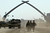 U.S. Army soldiers walk near a massive arch of swords at Saddam Hussein's military parade grounds on Friday, April 11, 2003. (AP Photo/John Moore)