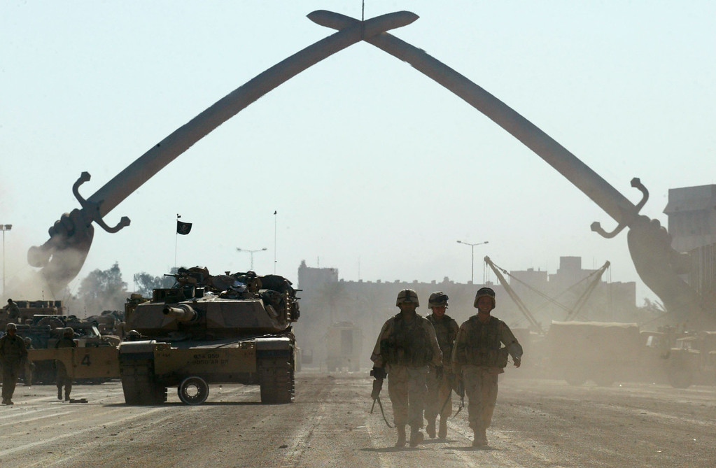 Description of . U.S. Army soldiers walk near a massive arch of swords at Saddam Hussein\'s military parade grounds on Friday, April 11, 2003. (AP Photo/John Moore)