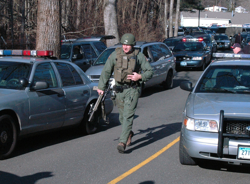 Description of . In this photo provided by the Newtown Bee, police officers are on the scene outside Sandy Hook Elementary School in Newtown, Conn., where authorities say a gunman opened fire, killing 26 people, including 20 children, Friday, Dec. 14, 2012. (AP Photo/Newtown Bee, Shannon Hicks)