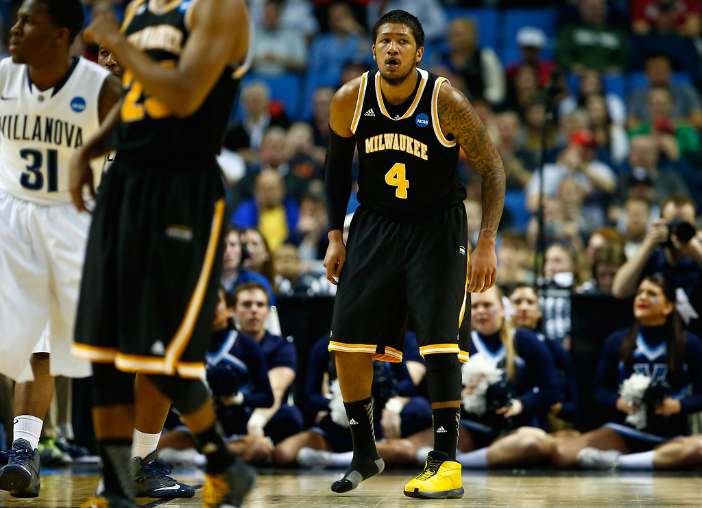 Description of . BUFFALO, NY - MARCH 20: Malcolm Moore #4 of the Milwaukee Panthers plays defense after losing his shoe against the Villanova Wildcats during the second round of the 2014 NCAA Men's Basketball Tournament at the First Niagara Center on March 20, 2014 in Buffalo, New York.  (Photo by Jared Wickerham/Getty Images)